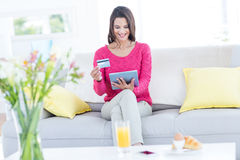 Smiling beautiful brunette doing online shopping on the couch Royalty Free Stock Photography