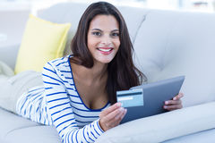 Smiling beautiful brunette doing online shopping on the couch Stock Photos