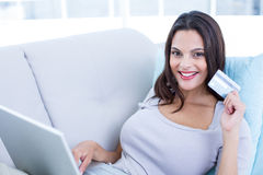 Smiling beautiful brunette doing online shopping on the couch Royalty Free Stock Photos