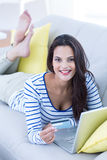 Smiling beautiful brunette doing online shopping on the couch Stock Photography