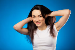 Smiling beautiful brunette girl in white t-shirt over blue backg Stock Images