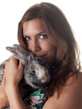 Smiling beautiful brunette holding and petting her bunny Stock Images