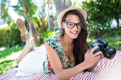 Smiling beautiful brunette lying on the blanket and taking pictures Royalty Free Stock Photos