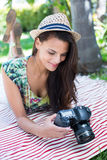 Smiling beautiful brunette lying on the blanket and taking pictures Royalty Free Stock Images