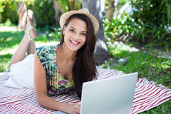 Smiling beautiful brunette lying on the blanket and using her laptop Stock Photos