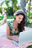 Smiling beautiful brunette lying on the blanket and using her laptop Stock Photography