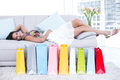 Smiling beautiful brunette lying on the couch with shopping bags around her Stock Photo