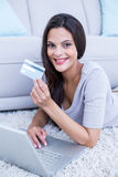 Smiling beautiful brunette lying on the floor and doing online shopping Stock Photos