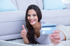 Smiling beautiful brunette lying on the floor and doing online shopping Royalty Free Stock Image