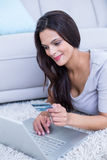 Smiling beautiful brunette lying on the floor and doing online shopping Stock Photography