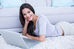 Smiling beautiful brunette lying on the floor and using her laptop Stock Photography