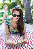Smiling beautiful brunette lying and reading a book. With palm tree behind her stock image