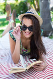 Smiling beautiful brunette lying and reading a book. With palm tree behind her royalty free stock photo