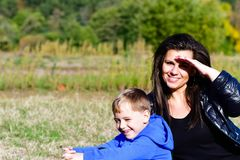 Mother and son in a park. Smiling  beautiful brunette outdoor with cute smiling boy in a park Royalty Free Stock Photo