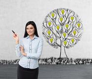 A smiling beautiful brunette is pointing out something by her hand. A sketch of a tree with light bulbs is drawn on the concrete w Stock Image