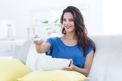 Smiling beautiful brunette relaxing on the couch with bowl of popcorn and changing tv station Stock Image