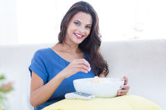 Smiling beautiful brunette relaxing on the couch with bowl of popcorn stock photo
