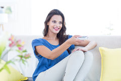 Smiling beautiful brunette relaxing on the couch and changing tv station Stock Images