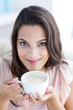 Smiling beautiful brunette relaxing on the couch and holding mug Stock Photos