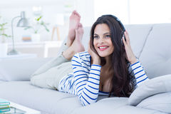 Smiling beautiful brunette relaxing on the couch and listening music Royalty Free Stock Photo