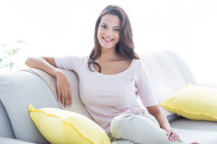 Smiling beautiful brunette relaxing on the couch and looking at camera stock photography