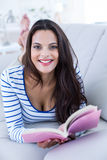 Smiling beautiful brunette relaxing on the couch and reading a book Stock Photo