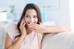 Smiling beautiful brunette relaxing on the couch and speaking on the phone Royalty Free Stock Photo