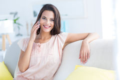 Smiling beautiful brunette relaxing on the couch and speaking on the phone Stock Photo