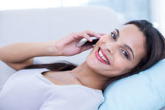 Smiling beautiful brunette relaxing on the couch and speaking on the phone Stock Image