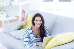 Smiling beautiful brunette relaxing on the couch and using her laptop Royalty Free Stock Images