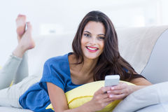 Smiling beautiful brunette relaxing on the couch and using her phone Stock Photography