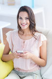 Smiling beautiful brunette relaxing on the couch and using her phone Royalty Free Stock Photo