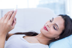 Smiling beautiful brunette relaxing on the couch and using her phone Royalty Free Stock Image