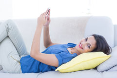 Smiling beautiful brunette relaxing on the couch and using her phone Stock Images