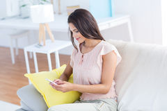Smiling beautiful brunette relaxing on the couch and using her phone Royalty Free Stock Images