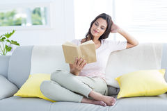 Smiling beautiful brunette relaxing and reading a book on the couch Stock Photo