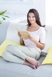 Smiling beautiful brunette relaxing and reading a book on the couch Royalty Free Stock Photos