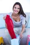 Smiling beautiful brunette sitting on the couch with shopping bags Royalty Free Stock Photos