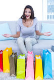 Smiling beautiful brunette sitting on the couch with shopping bags Royalty Free Stock Image
