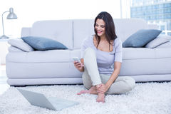 Smiling beautiful brunette sitting on the floor and using her phone Stock Photos