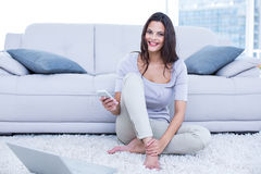 Smiling beautiful brunette sitting on the floor and using her phone. In the living room Royalty Free Stock Image