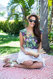 Smiling beautiful brunette sitting and reading a book. With palm tree behind her stock image