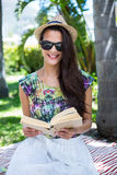 Smiling beautiful brunette sitting and reading a book. With palm tree behind her royalty free stock images