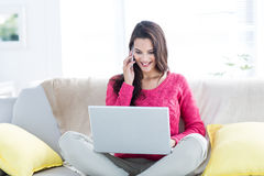 Smiling beautiful brunette speaking on the phone while using laptop Stock Image