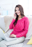 Smiling beautiful brunette speaking on the phone while using laptop Stock Photography