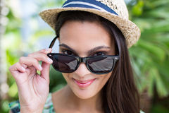 Smiling beautiful brunette wearing straw hat and sun glasses. With palm tree behind her Royalty Free Stock Image