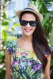Smiling beautiful brunette wearing straw hat and sun glasses. With palm tree behind her Stock Photos