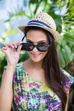 Smiling beautiful brunette wearing straw hat and sun glasses. With palm tree behind her Stock Photography