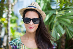 Smiling beautiful brunette wearing straw hat and sun glasses. With palm tree behind her Royalty Free Stock Photos