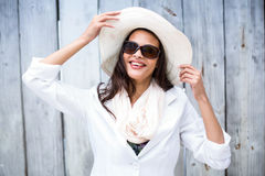 Smiling beautiful brunette wearing straw hat and sun glasses. On wooden plank background Stock Image